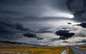 Обои дорога, поле, забор, буря, серые облака