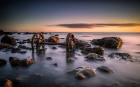Обои море, закат, камни, колёса