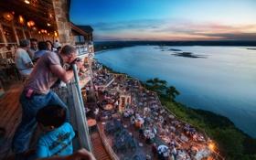 Обои закат, люди, побережье, столы, фонари, фотограф, ресторан
