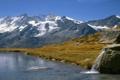 Картинка заснеженные, берег, трава, ключик, горы, озеро, камни